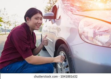 Asian women car tire air check for good pressure before go trip
