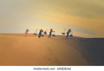 Asian women carrying baskets on her shoulders in the desert at sunset or sunrise time, Mui Ne, Vietnam.Asian women is walking and carry basket.