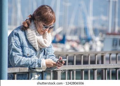 Asian women in casual using smart phone,working or playing social network,play Mobile Games and web site in park