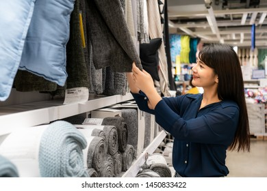Asian women are choosing to buy new carpet in the mall. Shopping for groceries and housewares are needed in markets, supermarkets or big shopping centres.