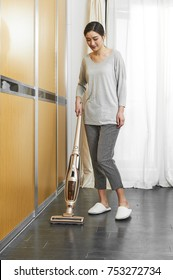 Asian women clean the bedroom with a cordless vacuum cleaner