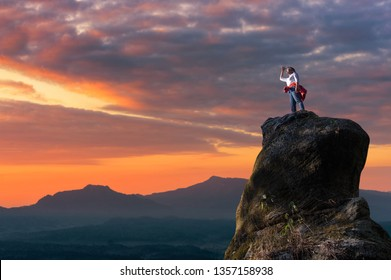 Asian women climbers or backpackers are standing, looking out through the tall treetops on the rocky peaks at sunset, success and winner, leader concept.