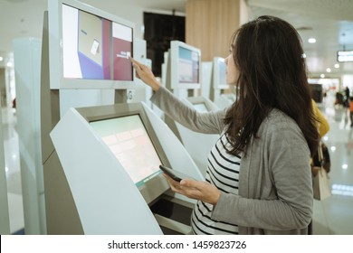 Asian women confirm the payment of the overweight of the goods carried using computer