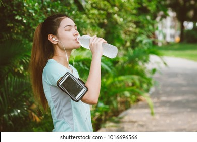Asian women are drinking the cool water in the park, woman listening to music on running Belt and running out.