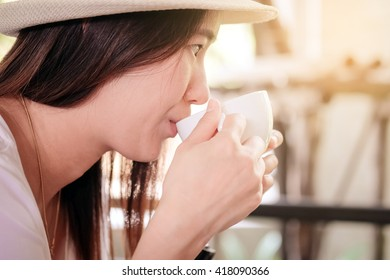 Asian women are drinking hot coffee from a cup.