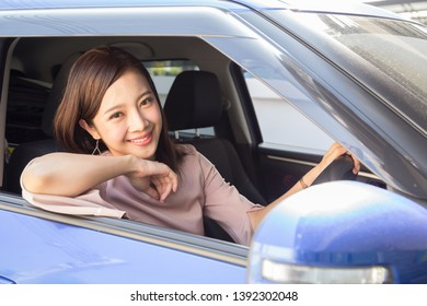 Asian women driving a car and smile happily with glad positive expression during the drive to travel journey, People enjoy laughing and relaxed happy woman on road trip vacation concept, Thai model
