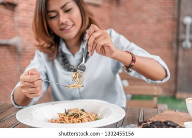 Asian women eating delicious,Focus on hand.
