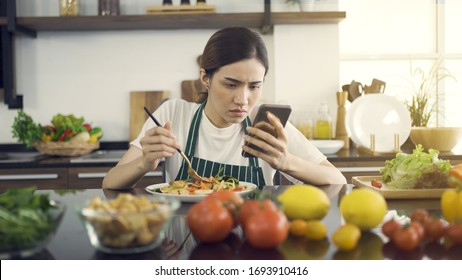 Asian Women Eating Salad While Sitting in Modern Kitchen.And looking at the news with a serious expression.While in the house to be detained during an epidemic Coronavirus(Covid-19).