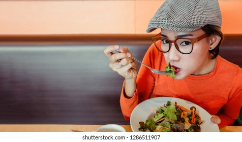 Asian women are eating salads at restaurants in a happy mood..Focus on face