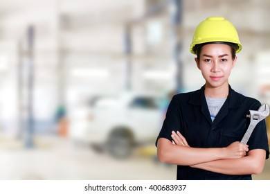 Asian women engineer holding a wrench in hand, prepared for the repairs cars on lifts in small service station for background
