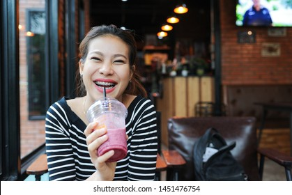 Asian women enjoy drinking smoothie frappe in cafe,Asian girl Smile while wearing braces,selective focus