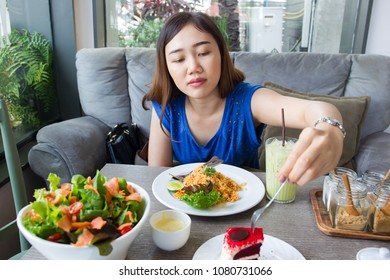 Asian women enjoying eating a cake and other food on the table.