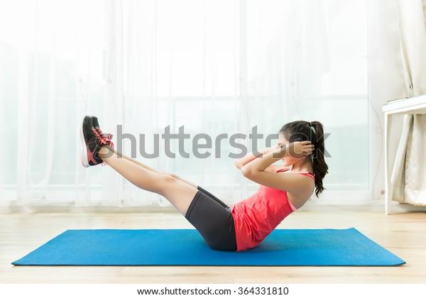 アジアの女性は自宅で運動をしています。腹部の運動は座り込みです。