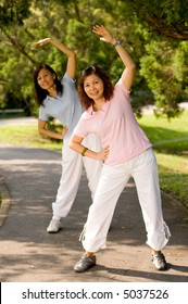 Asian women exercising in a park in the sunshine