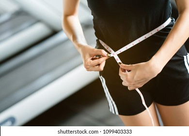 Asian women in fitness uniform And it is using the waist line to see if the exercise makes the body as intended or not. Caring for the body will be healthy and free from disease. close up for hand