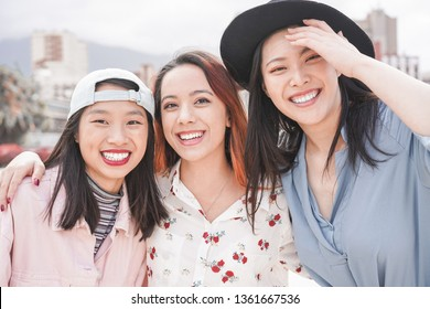 Asian women friends having fun outdoor - Happy trendy girls laughing together - Millennial generation, bonding, friendship and gathering concept - Focus on faces