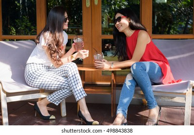 Asian women friendship talking in outdoor coffee cafe - young female student friend lifestyle portrait