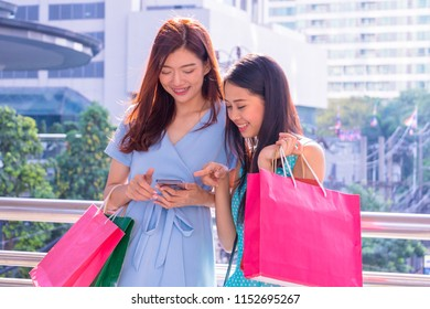 Asian women go shopping .They are shopping online on the mobile phone.They are  standing in town.They smile and they hold some pieces of paper and bags.Photo concept  Shopping and relax time.