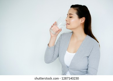 Asian Women hand is holding glass of water with pure water. Drinking of clean water and the temperature of 6-8 glasses per day will make skin of the body not wrinkled before age. And good for health