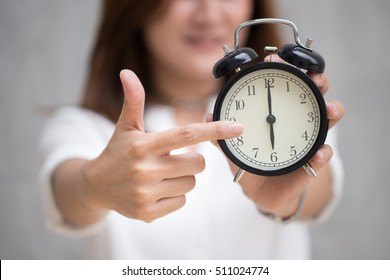 Asian women hand and point finger to retro clock times at 6 o'clock, It's time to do something concept