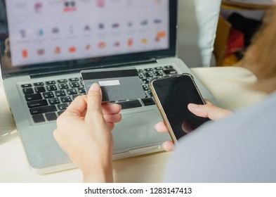 asian women hands holding credit card and smart phone for online shopping at home.
