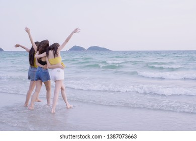 Asian women happy Group Friends  enjoy summer vacation and walking on the beach