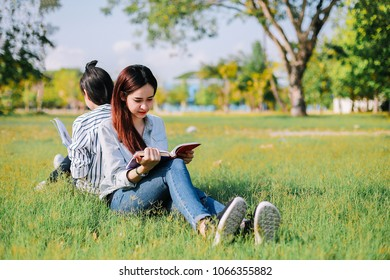 Asian women are happy and relaxed by reading book on green grass before attending class in the morning.