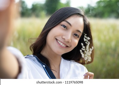 Asian women happy smile  taking photos and Selfie on relaxing time at the meadow and grass