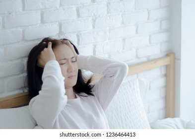 Asian women are headache severely.Lady wake up in the morning with migraine. Insomnia results in headaches when awakened.Young girl sitting on a stressed bed. In her bedroom.She was sick.