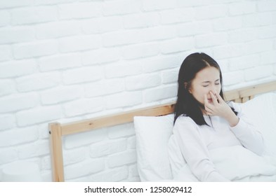 Asian women are headache severely.Lady wake up in the morning with migraine. Insomnia results in headaches when awakened.Young girl sitting on a stressed bed. In her bedroom.She was sad.