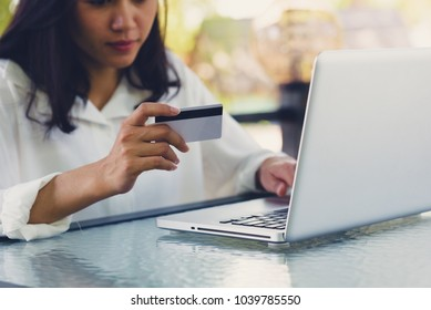 Asian women holding  credit card to payment and using laptop to purchasing online. Online shopping concept.