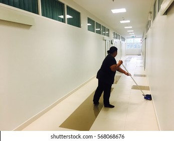Asian women janitor mopping floor in hallway of new school building. Cleaner janitorial service.