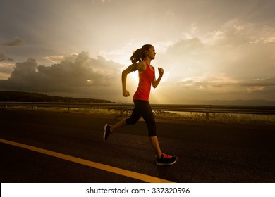 Asian women was jogging in the morning.and listens to music while running
