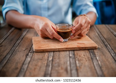 Asian women are lifting a cup of coffee to drink.Focus on hand