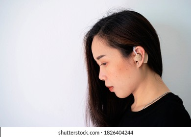 Asian women listening with her hand on an, Hearing test showing ear of young woman