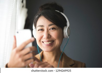 Asian women listening to music with headphones