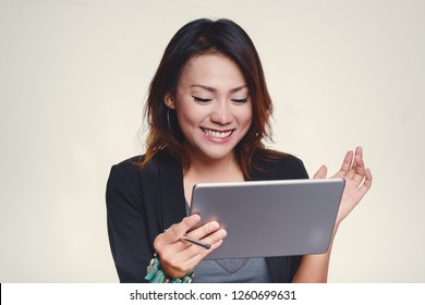 Asian women look at his iPad with a happy mood.Focus on the face.