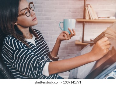 Asian women are looking at her coffee mug with interest.Focus on face