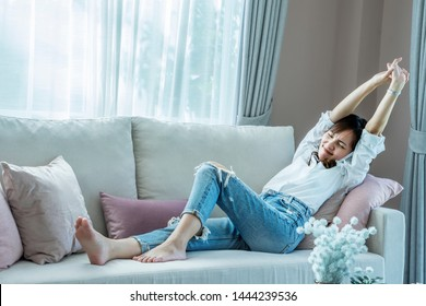 Asian women lying in the living room and stretch after feeling arm aches and relax on sofa in  home.Relaxation concept.