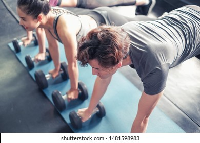 Asian women and man working out at gym center push up exercise with dumbbell