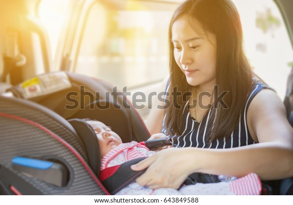 Asian women Mother takes care about her daughter in a car, helps her child fasten little young baby with car seat safety belt for infant,parent is keeping safe when riding in a vehicle on road.