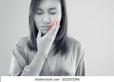 Asian women in nightwear and robe suffering from toothache while standing against grey background, Tooth Pain And Dentistry, Dental Care And Health Concept