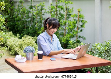 Asian women play notebooks and listen to music in the garden.