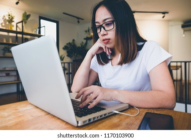 Asian women play relaxing laptop listening happily.