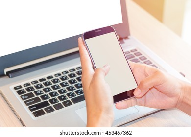 Asian women are playing phone screen on a white wooden table with a laptop in the morning light.