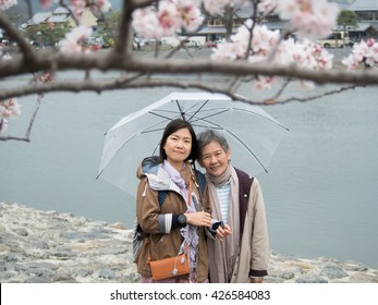 Asian women portrait - Senior mother and adult daughter with umbrella looking to the camera at Nishikyo-ku, Kyoto, Japan