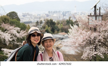 Asian women portrait - Senior mother and adult daughter looking and smiling to the camera. Background is Landscape Kyoto shooting from Kiyomizu-dera Temple, Kyoto, Japan