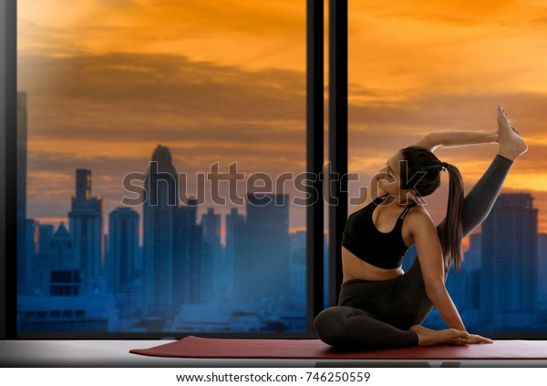 Asian women practicing yoga on sunset scene of skyscrapers background