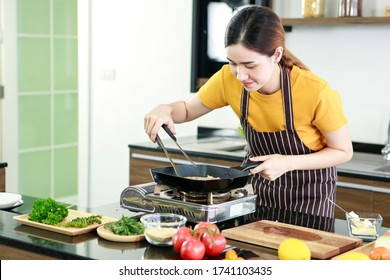Asian women present fresh food. Shot housewife trying to cooking and showing steak in pan in kitchen in house to take picture for sell food box online. Work from home / Stay at home / covid19 concept