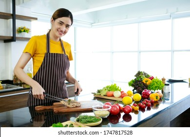 Asian women present fresh food. Housewife trying to cooking and showing pork of steak in kitchen in house to take picture for sell food box online. Work from home / Stay at home / covid19 concept